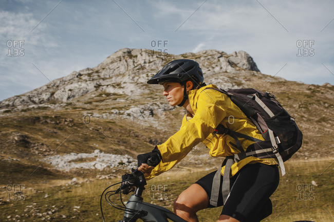 Mid adult woman with backpack riding electric bicycle on mountain at Somiedo Natural Park- Spain