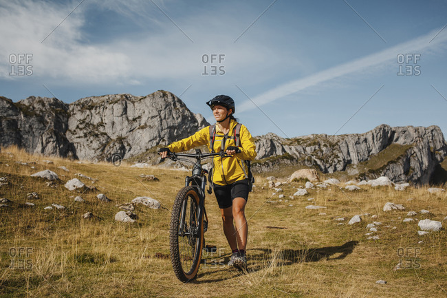 Mid adult woman holding bicycle while against mountain at Somiedo Natural Park- Spain