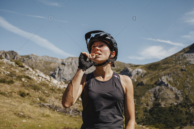 Woman wearing cycling helmet eating biscuit while standing against mountain at Somiedo Natural park- Spain