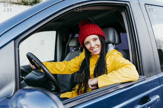 Smiling woman driving car during road trip