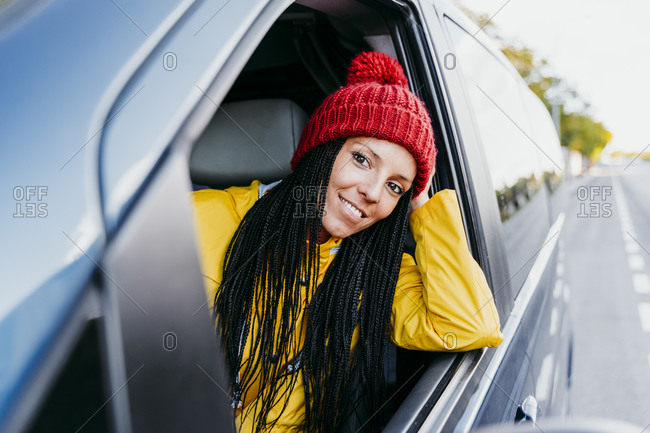 Woman with hand in hair looking out of car window during road trip