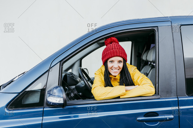Smiling woman with arms crossed looking through car window during road trip