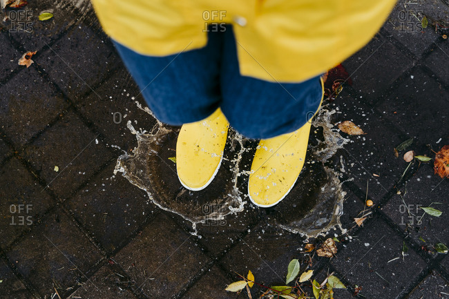 Woman wearing yellow boots jumping on puddle during rainy season