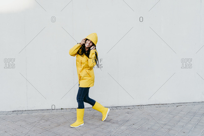 Smiling woman wearing raincoat standing on footpath against gray wall