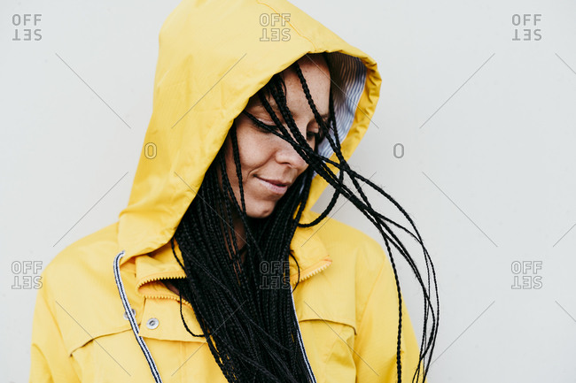 Woman wearing raincoat looking down against gray wall
