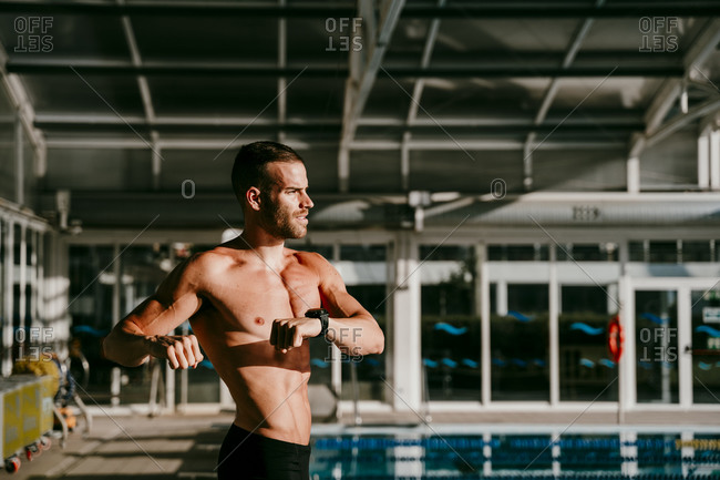 Shirtless male swimmer doing warm up exercise at poolside