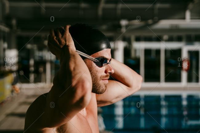 Handsome male swimmer preparing for swimming on sunny day