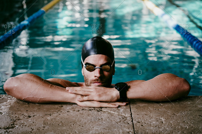 Professional male swimmer leaning at poolside