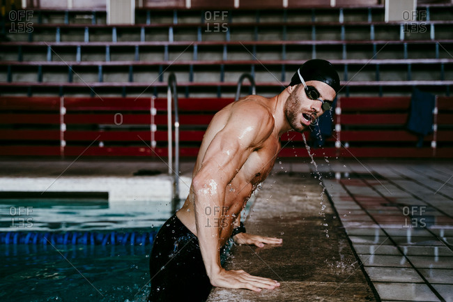 Shirtless young male swimmer leaning on poolside