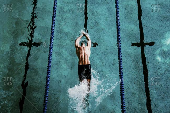 Male professional swimmer doing backstroke in swimming pool