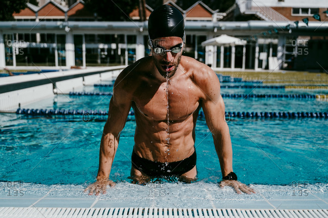 Muscular male swimmer getting out from swimming pool on sunny day
