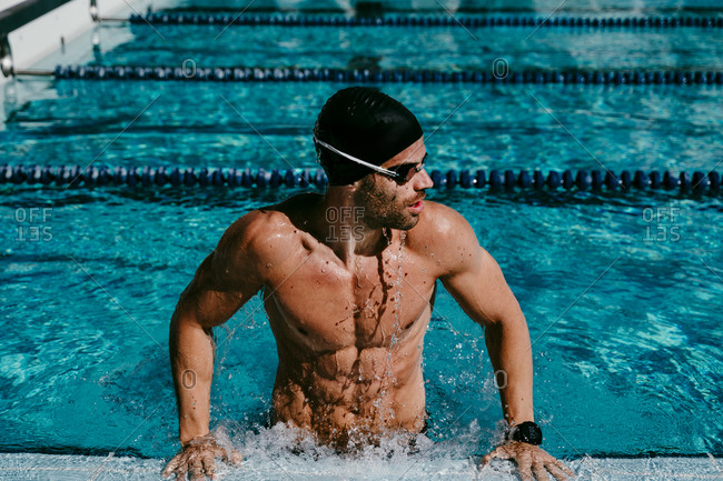 Muscular male swimmer looking away while standing at poolside