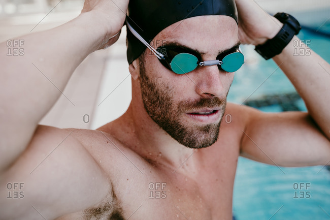 Handsome male swimmer adjusting swimming goggles
