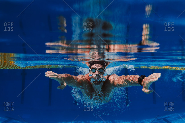 Professional male swimmer practicing underwater swimming in pool