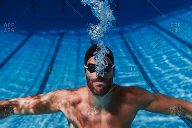 Professional young male swimmer swimming underwater