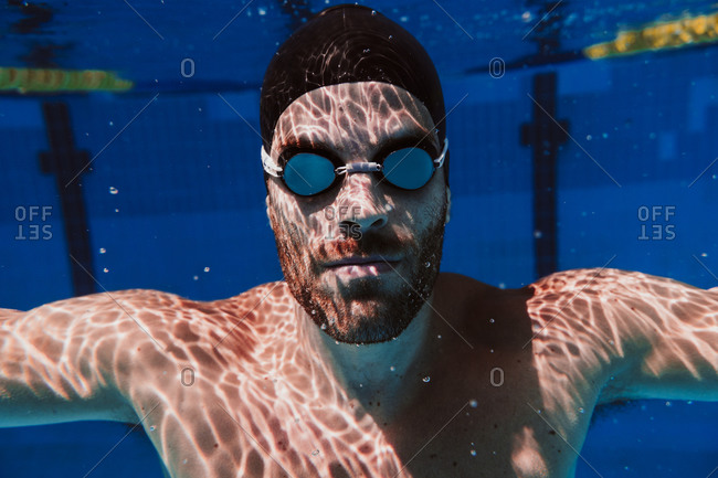Young male swimmer swimming underwater in pool