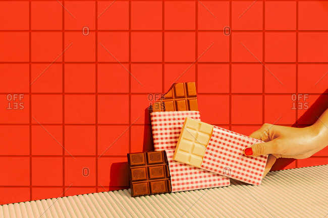 Woman hand putting chocolate bar against red tile wall
