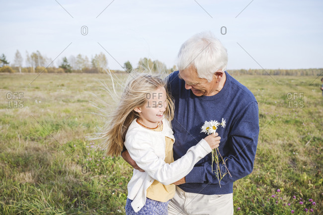 Happy grandfather with granddaughter holding chamomile flowers on field