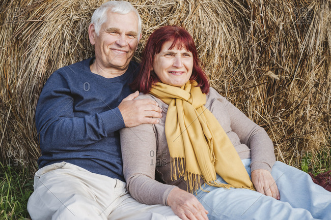 Happy senior couple resting against hay bale at field