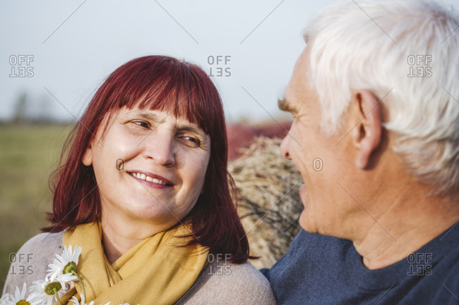 Smiling senior couple looking at each others while spending leisure time on field