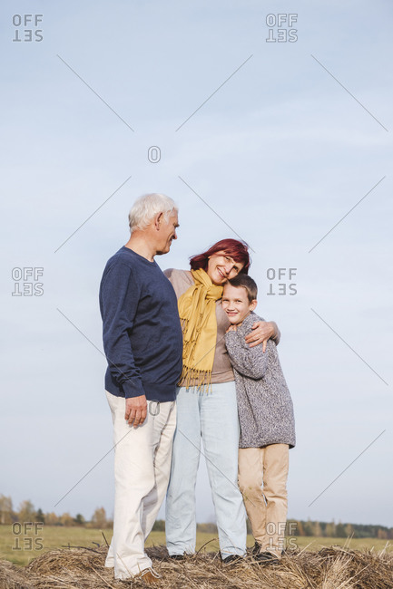 Grandmother embracing grandson while standing on haystack
