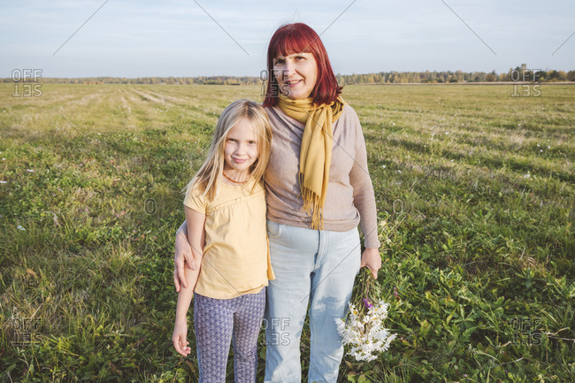 Senior woman with granddaughter standing at field