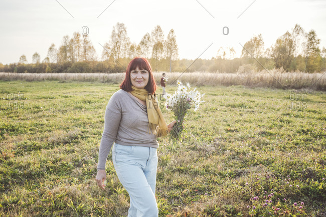 Senior woman walking with bouquet of chamomile flowers on field during sunny day