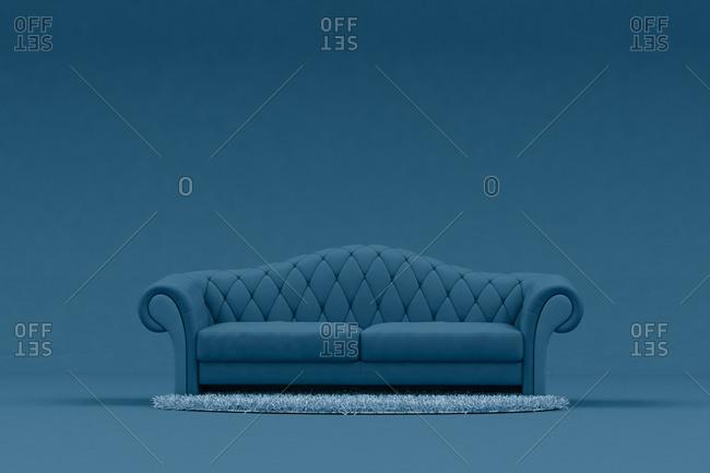 Blue sofa with light blue rug