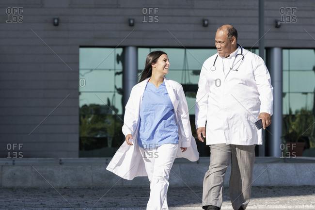 Doctors wearing lab coat walking against hospital