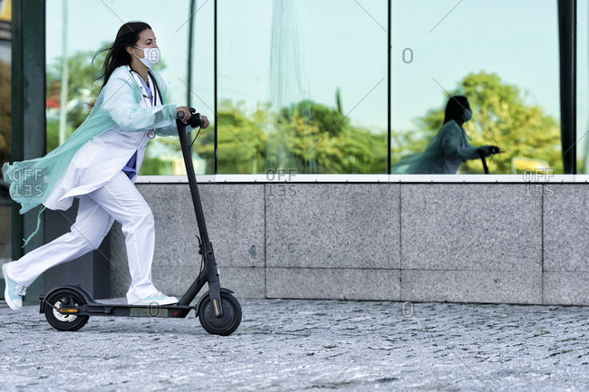 Young doctor in face mask and uniform riding push scooter while going to hospital during COVID-19