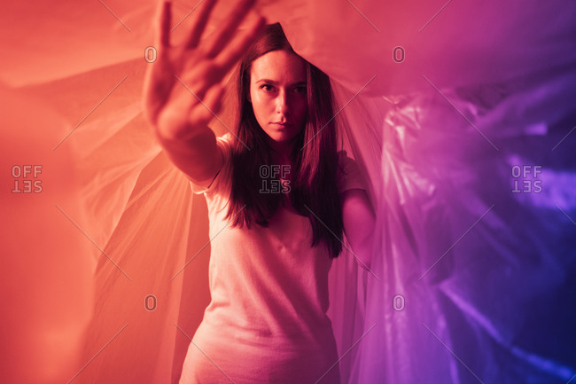 Young woman doing stop gesture while covered in plastic during coronavirus