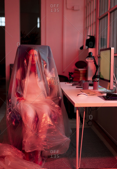 Woman sitting on chair covered in plastic at home office during COVID-19 crisis