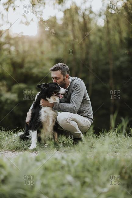 Man kissing his dog while crouching at park