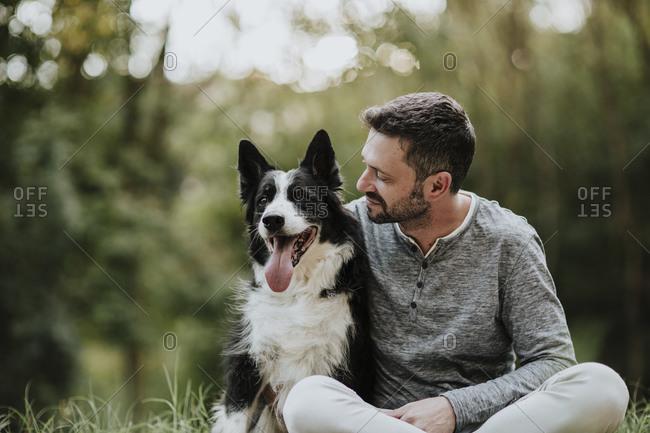 Smiling man staring dog while sitting at public park