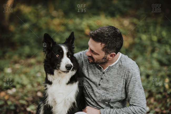 Man sitting with dog at public park