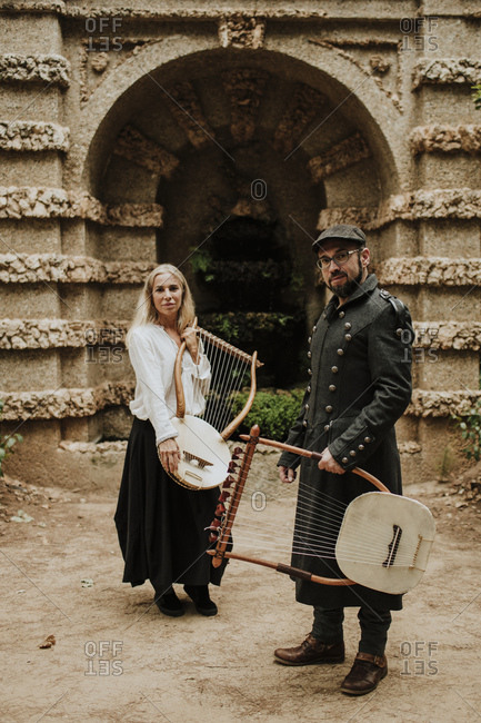 Male and female holding lyra musical instrument against built structure