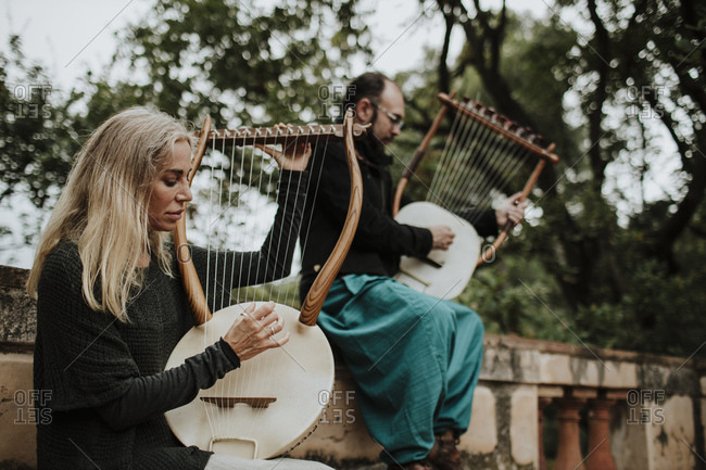 Female with male playing lyra musical instrument on bench