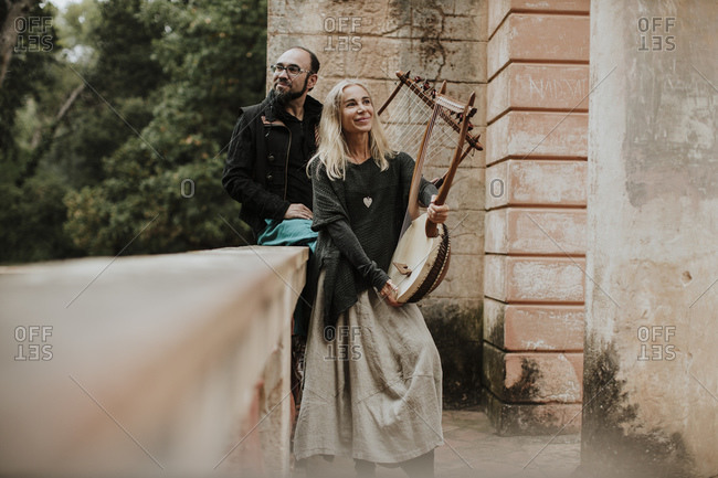 Smiling female with male holding lyra musical instrument by retaining wall