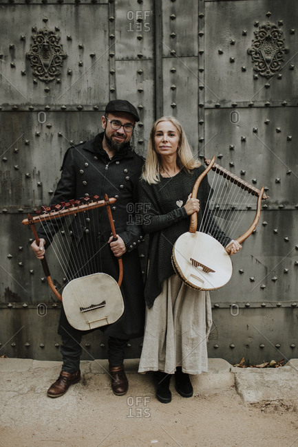 Male and female couple holding lyra musical instrument against metallic door