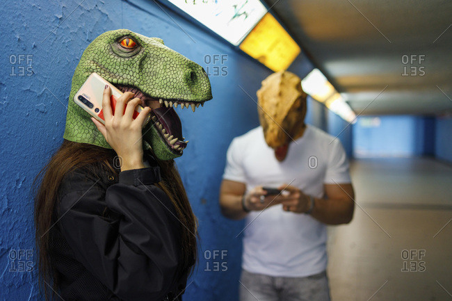 Female talking on smart phone by male friend while wearing dinosaur mask against blue wall