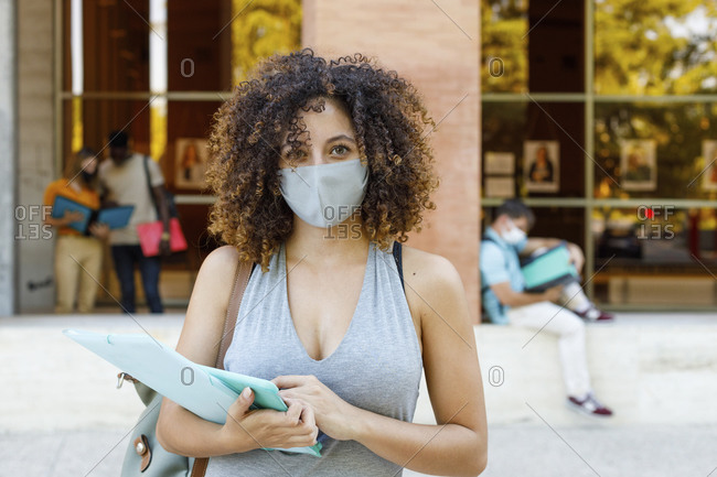 Young woman with documents wearing protective face mask while standing in university campus