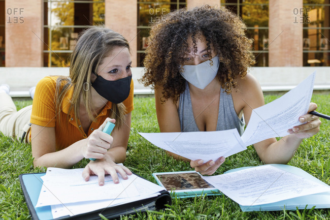 Female friends studying with protective mask while lying on grassy land in university campus