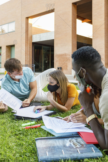 Female student with friends wearing safety mask while studying over grass in university campus