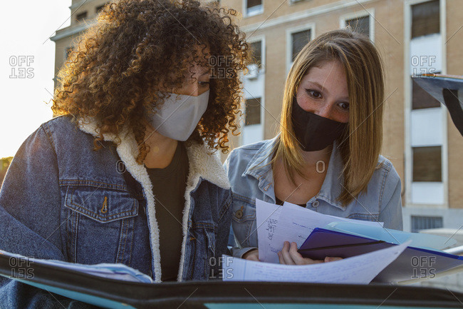Female friends studying with protective mask while standing against education building in university campus