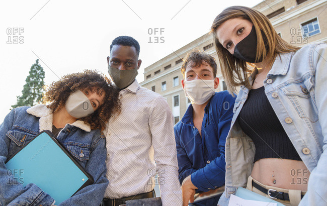 University students wearing protective mask while standing against education building