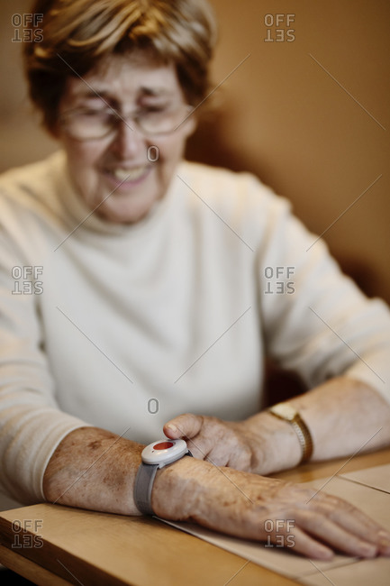 Senior woman pressing emergency button on wrist over table at home