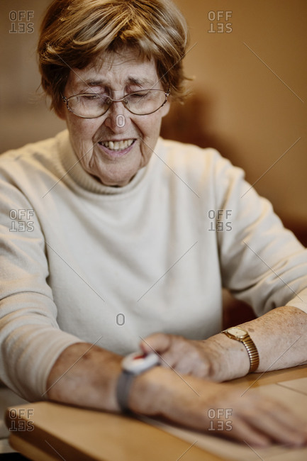 Wrinkled woman pressing emergency button on wrist over table at home