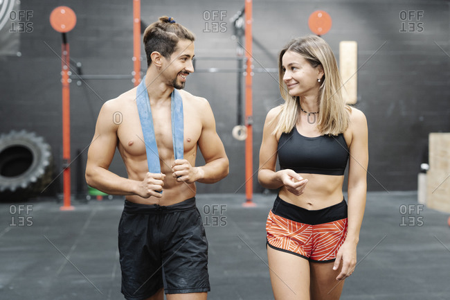 Smiling young couple looking at each other while walking against wall in exercise room