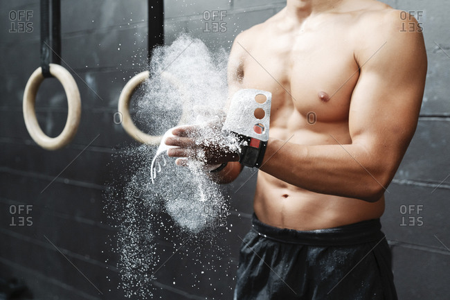 Close-up of shirtless young man dusting sports chalk with hands in gym