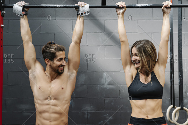 Smiling couple looking at each other while hanging on bars against wall in health club